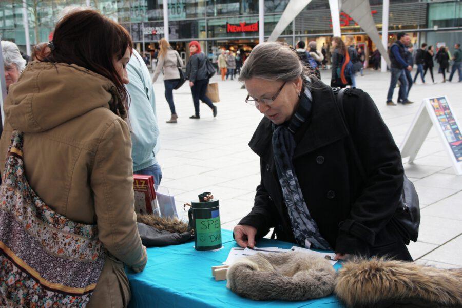 Eine Frau spricht am Stand mit einer Anima-Mitarbeiterin
