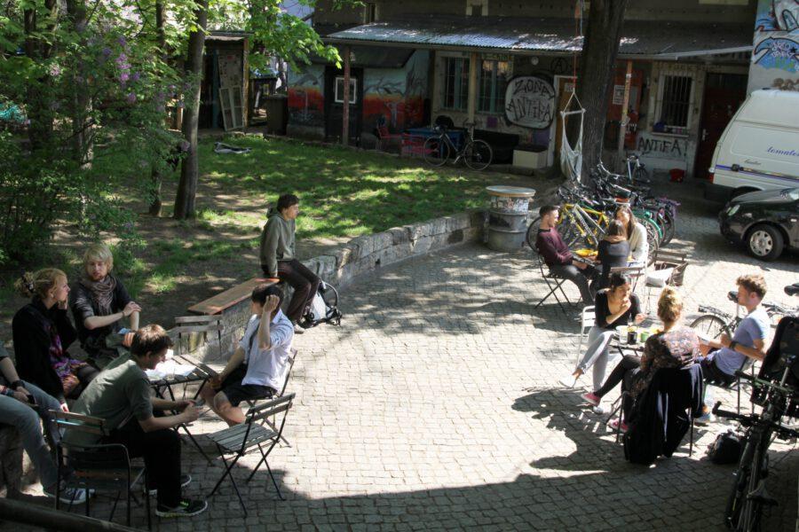 entspannte Brunch-Gäste an Tischen im Hof