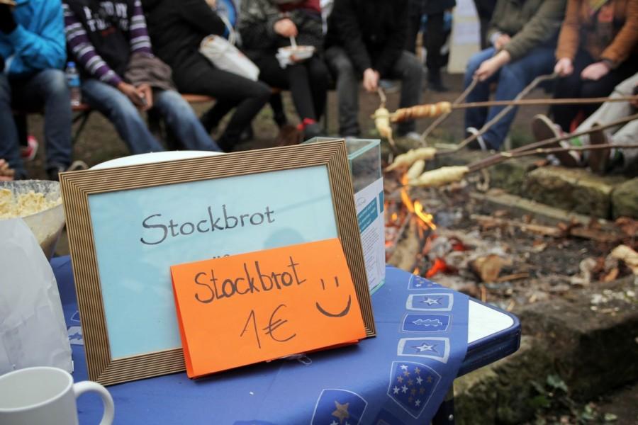 Schild für das Stockbrot mit Lagerfeuer im Hintergrund
