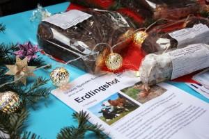 Tisch mit Stollen und einem Flyer vom Erdlingshof auf dem Weihnachtsmarkt in Leipzig