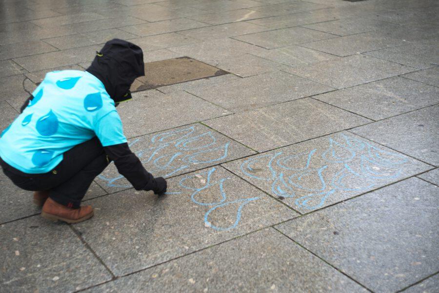 Aktive malt blaue Wassertropfen mit Kreide auf den Boden.