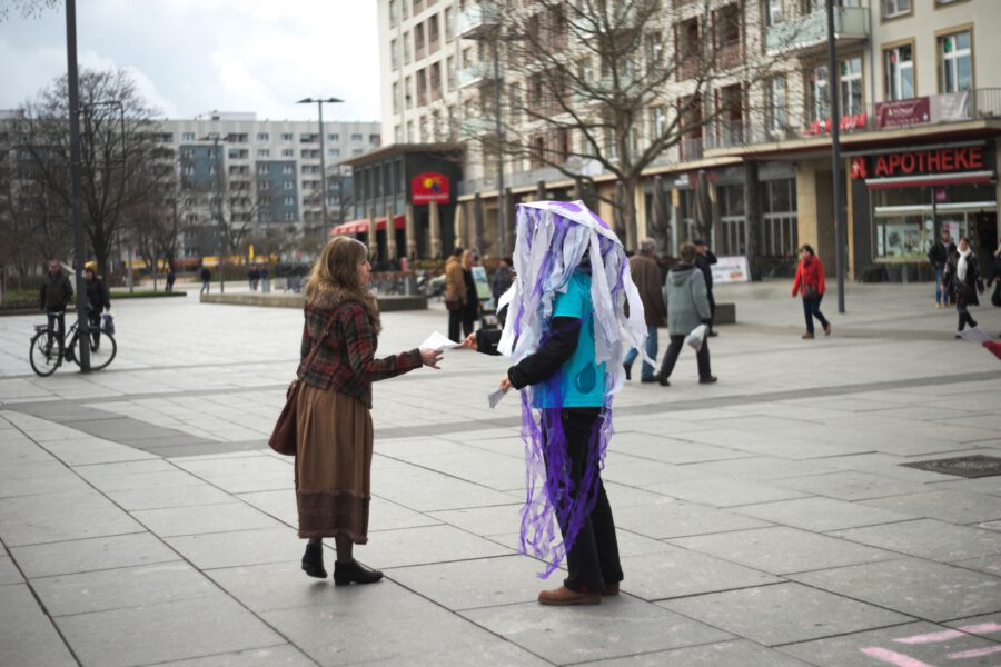 Aktive verteilt Flyer im Quallen-Kostüm