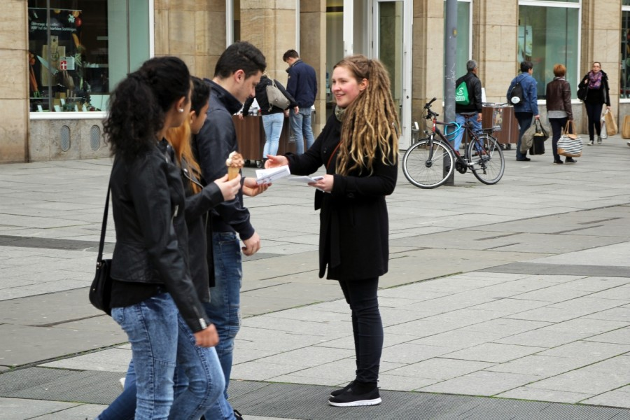 Flyer werden bei der Anti-Pelz-Aktion an Passantinnen verteilt.
