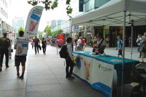 Aktivisten mit einem Stand und Movingboard in der Dresdner Innenstadt.