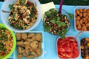 Verschiedene Salate, Tomaten und Gemüsebällchen auf einem Tisch.