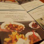Aufgeschlagene Flyer mit Bildern und Informationen über eine Auswahl veganerfreundlicher Restaurants.