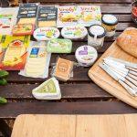 verschiedene Käsealternativen auf einem Tisch mit Brot und frischem Gemüse