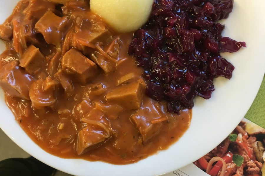 Ein Teller mit Seitangulasch mit Rotkraut und Klößen.