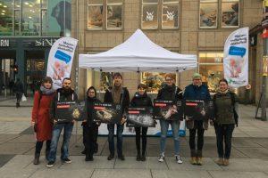 Aktive mit Schildern von Tieren in der Käfighaltung vor einem Stand der Albert Schweitzer Stiftung.